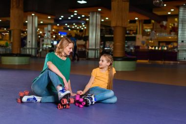 mother and little daughter sitting on roller rink together