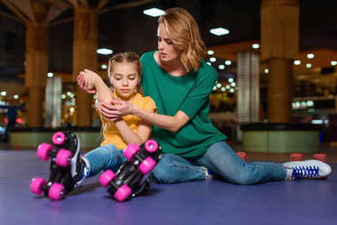 mother cheering up injured daughter on roller rink