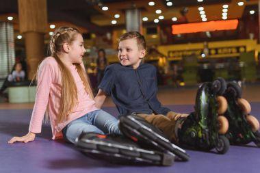 cute siblings in roller skates resting after skating on roller rink