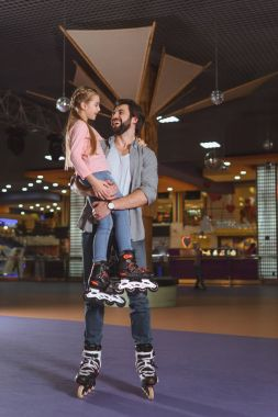 happy father holding daughter in roller skates on roller rink