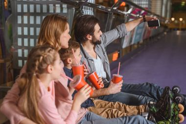 side view of family with drinks taking selfie while resting after skating on roller rink