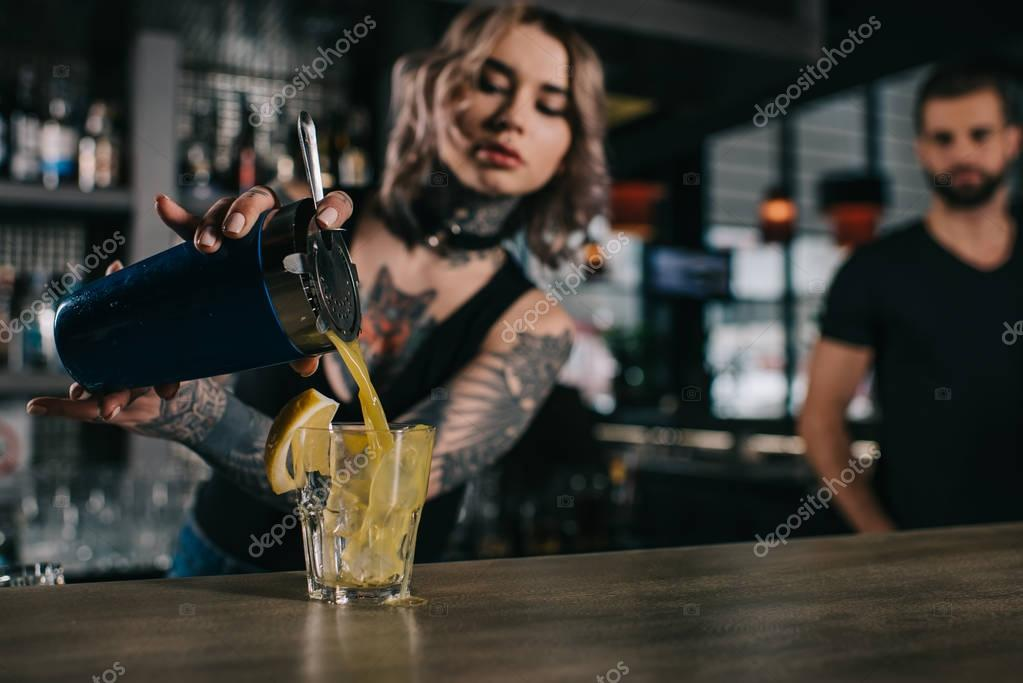 tattooed bartender preparing drink at bar
