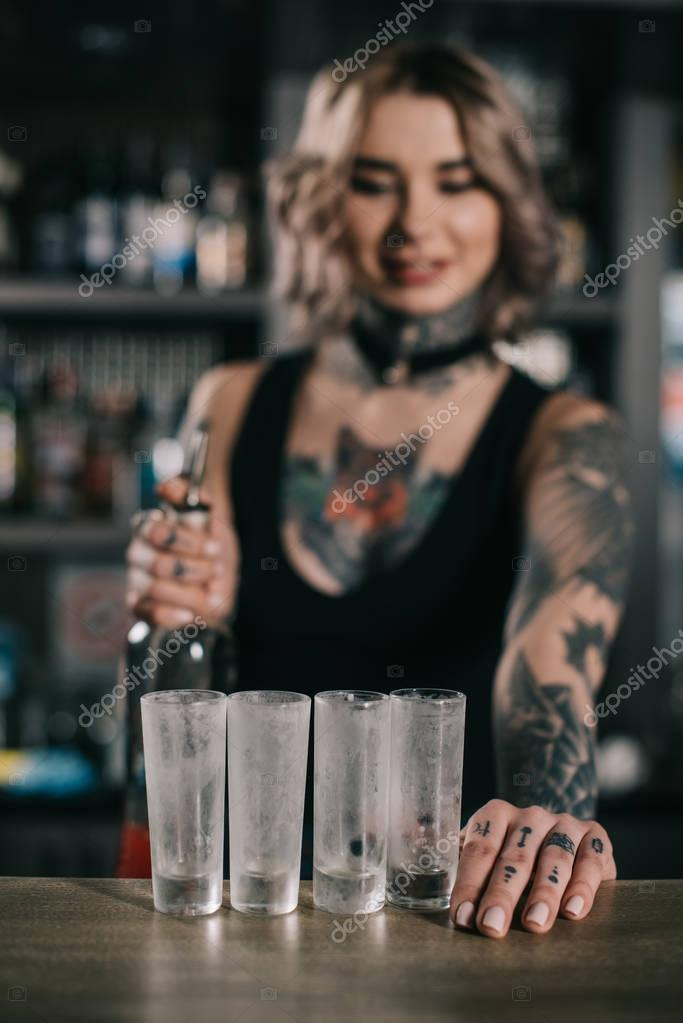 tattooed bartender looking at glasses for shot drinks