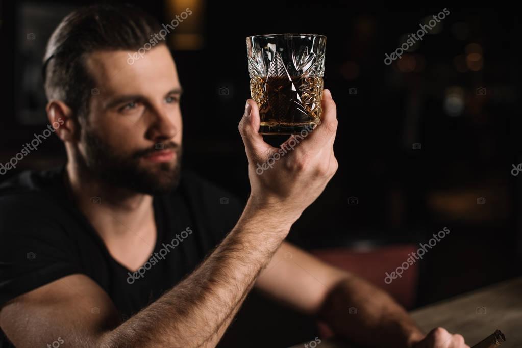 man sitting at bar counter and looking at glass of whiskey at bar