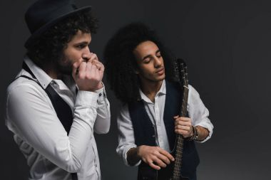 duet of musicians playing acoustic guitar and harmonica on black