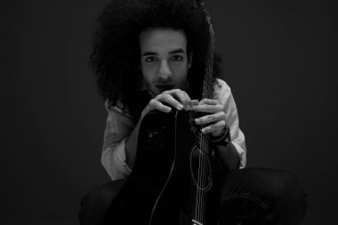 black and white portrait of young musician with acoustic guitar looking at camera