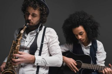 duet of musicians playing sax and guitar on black