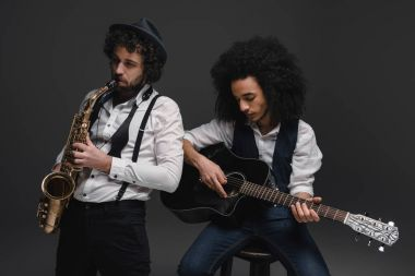 duet of musicians playing sax and acoustic guitar on black