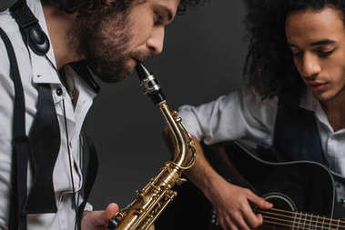 duet of jazzmen playing sax and acoustic guitar on black
