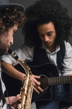 young duet of musicians playing sax and acoustic guitar on black