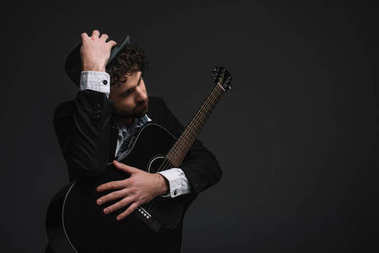 handsome musician in hat embracing his guitar on black