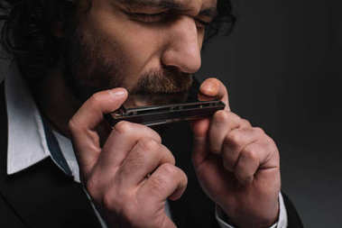 close-up portrait of expressive musician playing harmonica on black