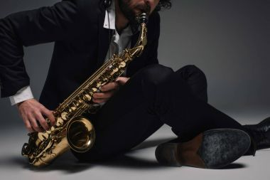 cropped shot of musician playing saxophone while sitting on floor