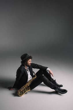 handsome musician sitting on floor with saxophone