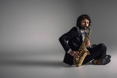 stylish musician playing saxophone while sitting on floor