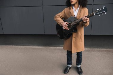 cropped shot of street musician playing guitar outdoors