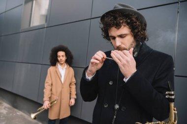 duet of street musicians playing harmonica outdoors