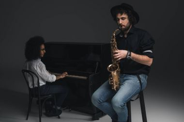 man playing saxophone while his partner playing piano blurred on background