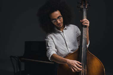 happy young musician playing standup bass