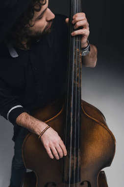 young handsome musician playing standup bass
