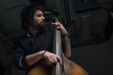 bottom view of young handsome musician playing contrabass