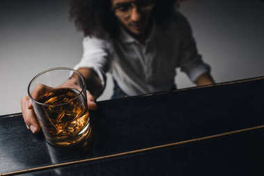 young man playing piano and reaching for glass of whiskey