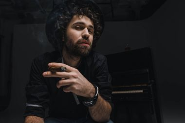 serious musician smoking cigar in front of piano on black