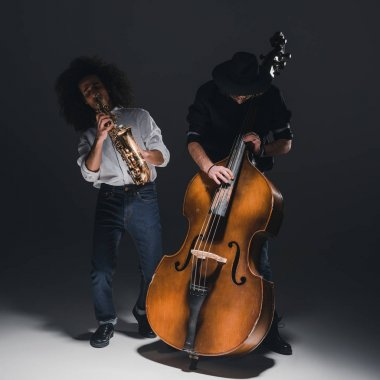 duet of young jazzmen playing trumpet and saxophone on black