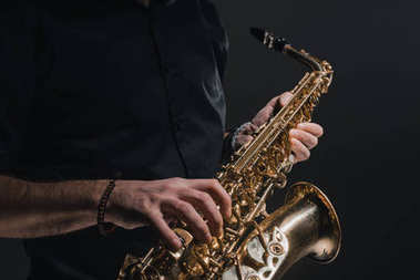 cropped shot of man playing saxophone on black