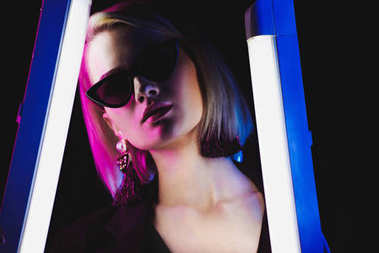 stylish attractive girl posing in sunglasses with two ultra violet lamps for fashion shoot, isolated on black
