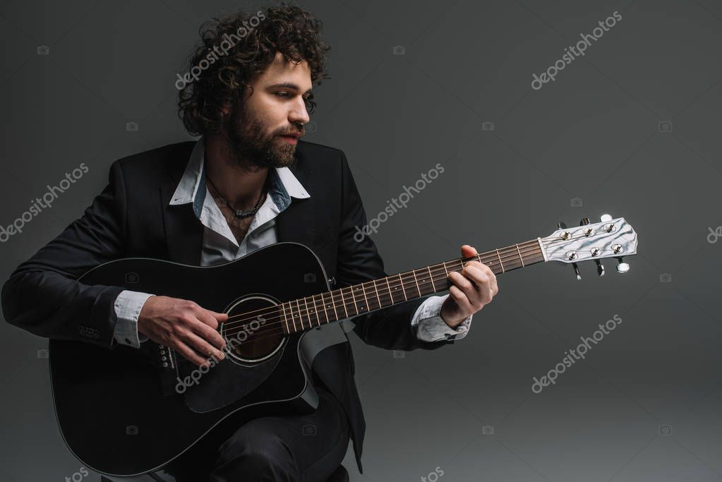 handsome musician playing acoustic guitar