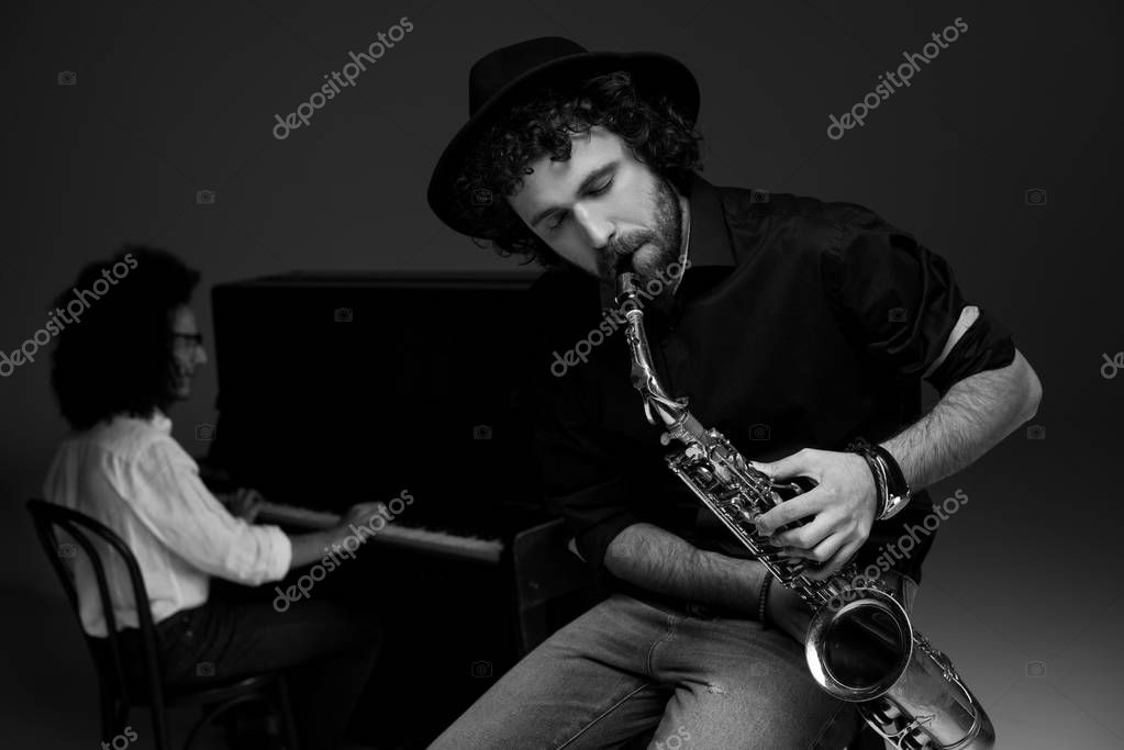 black and white shot of man playing saxophone while his partner playing piano blurred on background