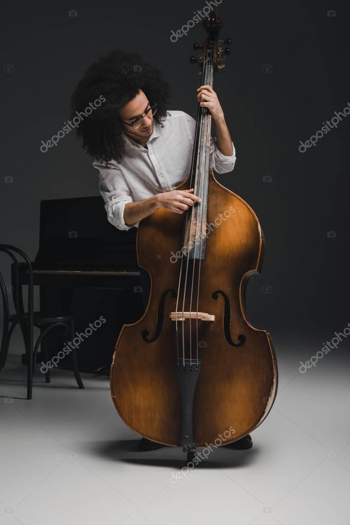 handsome young musician playing standup bass