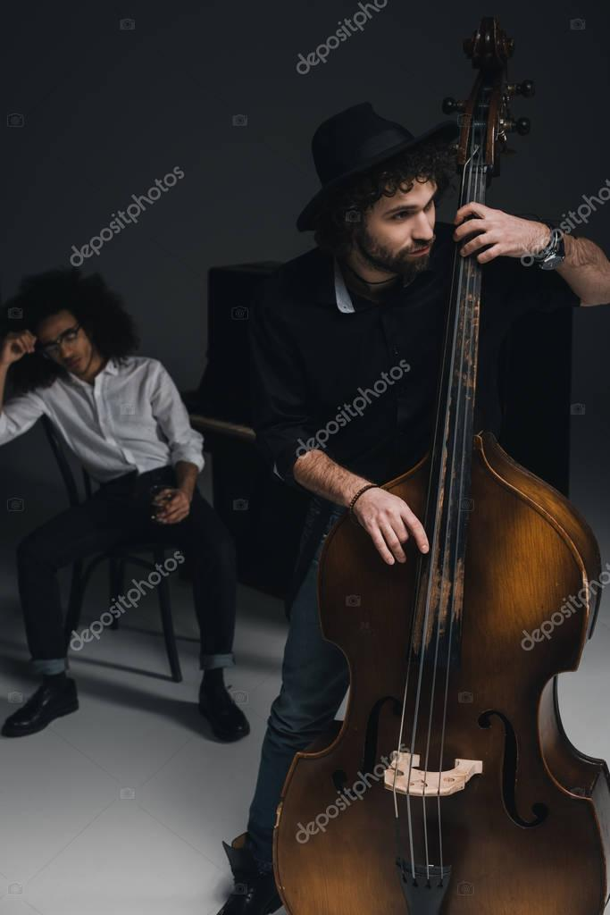 man playing violoncello while his partner sitting at piano with glass of alcohol blurred on background