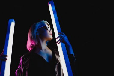 beautiful stylish model posing with two ultraviolet lamps for fashion shoot, isolated on black