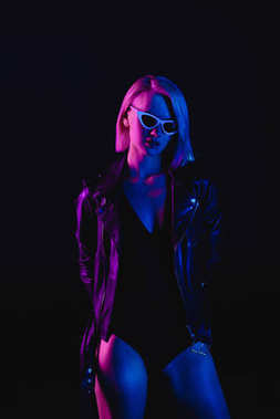 fashionable girl posing in black leather jacket and sunglasses, isolated on black