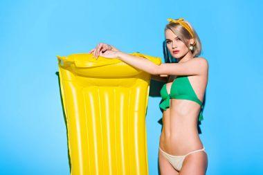 beautiful stylish girl posing in bikini with yellow inflatable mattress on blue