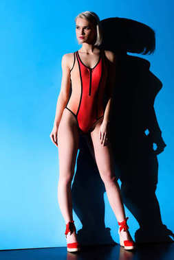 beautiful girl posing in trendy swimsuit, on blue for fashion shoot