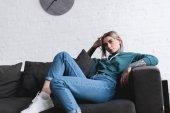 Fotografie krásná Tetovaný dívka sedí na gauči a koukal