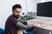 tetovált jóképű férfi, gazdaság mopszli és otthoni asztalnál ült