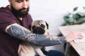 levágott kép tetovált jóképű férfi mopszli kutya otthon
