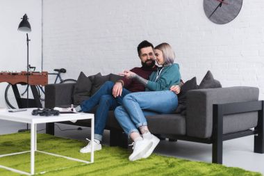 smiling tattooed couple hugging on sofa in living room