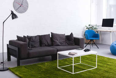 grey sofa and green carpet with tables in living room