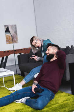 tattooed couple playing video game in living room