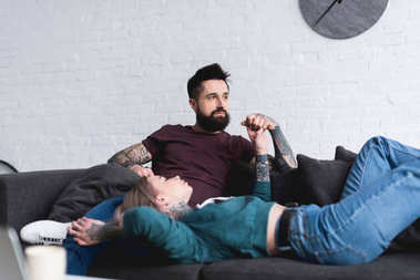 tattooed couple holding hands on sofa in living room