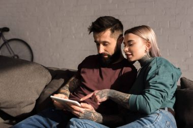 tattooed girlfriend pointing on something at tablet to boyfriend