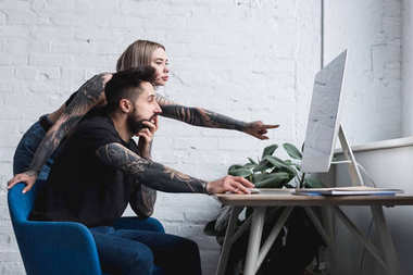tattooed girlfriend pointing on something at computer to boyfriend