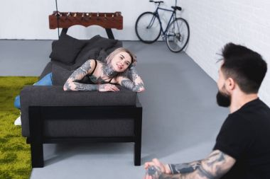 smiling tattooed girlfriend lying on sofa and looking at boyfriend at home