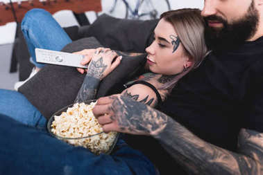 Cropped image of tattooed couple watching tv with popcorn at home stock vector