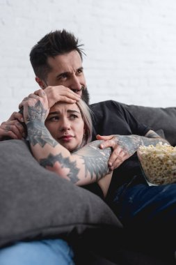 scared tattooed couple watching horror movie on sofa at home